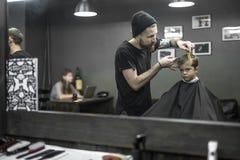 Ostrzyżenie mała chłopiec w zakładzie fryzjerskim Obraz Stock