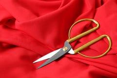 Ostrzy nożyce na czerwonej tkaninie Krawiectwa akcesorium fotografia stock