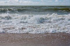 Ostsee mit Wellen, Sand und bewölktem blauem Himmel Lizenzfreie Stockfotografie