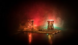 Osttee im traditionellen glasse und Topf auf schwarzem Hintergrund mit Lichtern und Rauche Ostteekonzept Armudu traditionelles Az Stockbilder