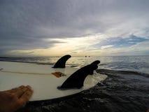 OSTTIMOR, INDONESIEN IM JANUAR 2017: Surfer greift das umgedrehte Surfbrett beim Warten den folgenden Satz von auf Wellen Lizenzfreie Stockbilder