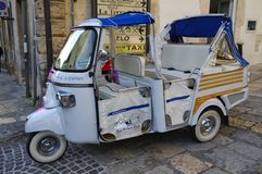 The touristic motor trike in the street of Ostuni town, The. OSTUNI, PUGLIA, ITALY - MARCH 28th, 2018: The touristic motor trike is waiting for passengers in the royalty free stock photography