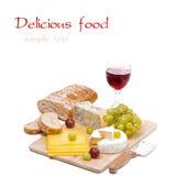 Ostuppläggningsfat, druvor, ciabatta och ett exponeringsglas av rött vin Royaltyfri Fotografi