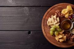 Ostuppläggningsfat: Parmesan, cheddar, gouda, gorgonzola, brie och annan med valnötter, oliv och honung på träbräde på royaltyfria bilder