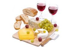Ostuppläggningsfat, druvor, bröd och två exponeringsglas av rött vin Royaltyfri Fotografi