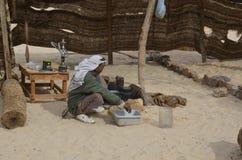 Ostwüste, Ägypten - 24. Januar 2013: Beduinischer Mann, der Lebensmittel in der Wüste zubereitet Stockfotos