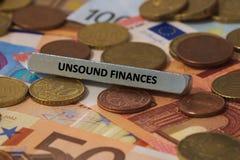 Osunda finanser - ordet skrivevs ut på en metallstång metallstången förlades på flera sedlar Royaltyfri Foto