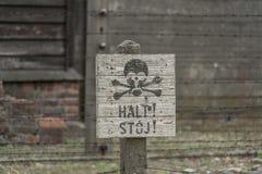 Oswiecim, 23-ье августа 2017: Остановите знак перед колючими загородками стоковое фото rf