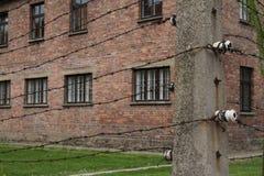 OSWIECIM Polen - Maj 09, 2015: Elektriskt staket och byggnader Arkivbild