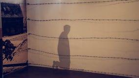 Oswiecim/Polen - 02 15 2018: Schatten auf der Wand eines knienden Mannes stockfotos