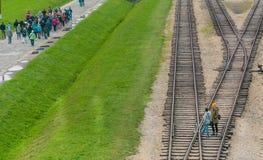 Oswiencim, Polen - September 21, 2019: De groepen Toeristen lopen volgens de treinlijn waar de wagens met aankwamen stock fotografie