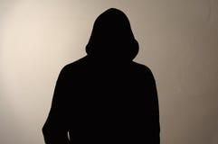 Osynlig man i huven Grå färgbakgrund Fotografering för Bildbyråer