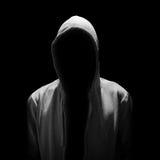 Osynlig man i huven som isoleras på svart backgrou Arkivfoto