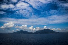 Oszałamiająco jaskrawy i bogaty zmrok - niebieskie niebo z chmurami, górami i oceanem, zdjęcia royalty free