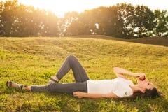 Oszałamiająco młodego brunetki łasowania jabłczany lying on the beach na trawie Zdjęcie Stock