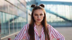 Oszałamiająco moda model z fryzurą i w czerwonych okularów przeciwsłonecznych stojakach przed szklaną ścianą i pozach dla kamery zdjęcie wideo
