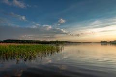 Oszałamiająco półmrok przy lata jeziorem z dynamicznymi chmurami zdjęcia stock