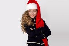Oszałamiająco piękna mała dziewczynka z długimi blondynami, ubierającymi w czerwonej nakrętce Święty Mikołaj i elegancki odziewa Obraz Stock
