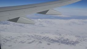 Oszałamiająco piękno pasmo górskie, nieznacznie zakrywający z śniegiem, przechodzi chmurami, widok od samolotowego okno zbiory