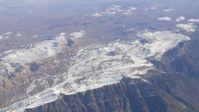 Oszałamiająco piękno pasmo górskie, nieznacznie zakrywający z śniegiem, przechodzi chmurami, widok od samolotowego okno zdjęcie wideo