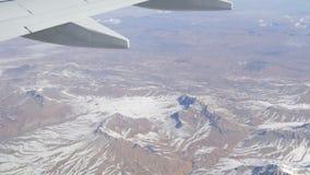 Oszałamiająco piękno pasmo górskie, nieznacznie zakrywający z śniegiem, przechodzi chmurami, widok od samolotowego okno zbiory wideo
