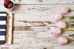Oszałamiająco różowi tulipany, lampasów notatniki i truskawki na światła białego nieociosanym drewnianym tle, Odbitkowa przestrze Fotografia Stock