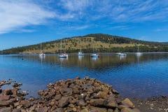 Oszałamiająco Tasmanian nabrzeżny krajobraz z jachtami i niebieskim niebem Zdjęcia Stock
