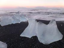 Oszałamiająco widok ogromne góry lodowa na czarnej piasek plaży pod pastelowych menchii zmierzchu niebem Fotografia Stock