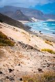 Oszałamiająco zdewastowany krajobraz piasek diuny i pustynne rośliny przed ocean fala na Baia Das Gatas w tle Zdjęcia Stock