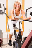 Oszałamiająco młoda kobieta używa ćwiczenie rower Obrazy Stock