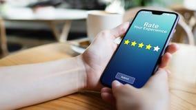 Oszacowywa twój doświadczenia zadowolenie klienta przeglądu Pięć gwiazdy na telefonu komórkowego ekranie błękitnawego biznesowego zdjęcia stock