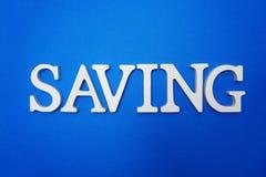 Oszczędzania abecadła listy na błękitnym tle obraz stock
