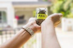 Oszczędzania i inwestyci pojęcia wizerunek Ręki trzyma pieniądze słój Fotografia Royalty Free