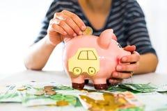 Oszczędzania pojęcie Kobiety ręka stawia pieniądze w prosiątko banku Selekcyjna ostrość Obrazy Stock
