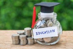 Oszczędzanie dla edukaci z monetami w słoju i absolwentów kapeluszowej etykietce a Zdjęcie Stock