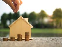 Oszczędzanie kupować dom który wręcza kładzenie pieniądze monet sterty dorośnięcia, oszczędzanie pieniądze lub pieniądze przyrost Obraz Stock