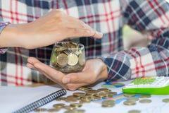 Oszczędzanie ochrona, gacenie pieniądze, zakończenie w górę żeńskich ręk zakrywa monety w szklanym słoju obraz stock