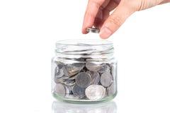 Oszczędzanie pieniądze, żeńska prawa ręka kładzenie monety sterta w słoju Fotografia Royalty Free