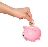 Oszczędzanie pieniądze, żeńska ręka stawia monetę w prosiątko banka odizolowywającego na bielu Obraz Royalty Free