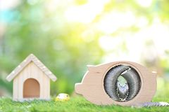 Oszczędzanie pieniądze dla przygotowywa w przyszłości i nowego domu pojęciu, prosiątko banka drewno z modela domem na naturalnym  obraz stock
