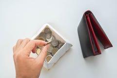 Oszczędzanie pieniądze pojęcie - kobieta stawia monetę od portfla w pudełku zdjęcie royalty free