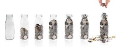 Oszczędzanie pieniądze pojęcie kolekcjonowanie monety w szklanej butelce Odizolowywa Zdjęcia Royalty Free