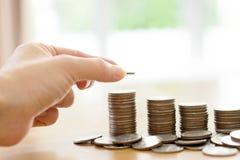 Oszczędzanie pieniądze pojęcie, Męski ręki kładzenia pieniądze monety sterty dorośnięcie zdjęcia royalty free