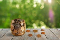 Oszczędzanie pieniądze w szklanej butelce na starym drewnianym stołowym przedpolu z zamazanym zielonym bokeh tłem obraz stock