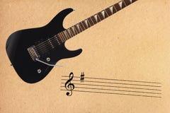 Oszukiwa elektryczną rockową gitarę i czerni przy wierzchołkiem szorstki kartonowy tło Obraz Stock