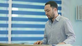 Otålig manlig patient som väntar på mottagandeskrivbordet stock video