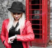 Otålig ung kvinna som kontrollerar hennes klocka Arkivbilder