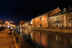 Otaru canal and warehouses, Hokkaido. OTARU, JAPAN  - APRIL 20, 2016: Beautiful Otaru canal and old warehouses with skyline reflection at night, Hokkaido Royalty Free Stock Images