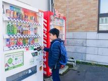 Otaru, Japan - October 19, 2017 : A boy selecting drink from automatic vending machine, at Otaru, Hokkaido, Japan. royalty free stock image