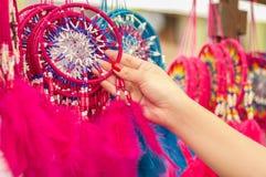 OTAVALO,厄瓜多尔- 2017年5月17日:关闭拿着一桃红色catchdreamer在她的手上的妇女,在五颜六色的市场上 免版税库存图片